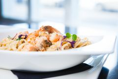 Creamy seafood pasta. With salmon, shrimp, mussels and Grana Padano cheese Royalty Free Stock Photos