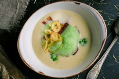 Creamy soup with bacon and green peas from the chef royalty free stock images