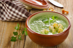 Creamy soup with  croutons on a wooden table. Stock Image