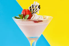 Creamy strawberry dessert on contrast background. Creamy strawberry dessert on contrast blue and yellow background. Sweet fruit souffle decorated with fresh red Stock Image