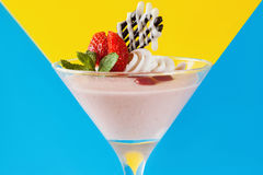 Creamy strawberry dessert on contrast background. Creamy strawberry dessert on contrast v-shaped blue and yellow background. Sweet fruit souffle decorated with Royalty Free Stock Image