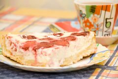 Creamy strawberry pie. Slice of creamy strawberry pie dessert on a plate with a coffee cup on the side Stock Photography