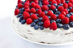 Creamy sweet cake with blueberries and raspberries. Creamy sweet cake with chocolate and cream, garnished with blueberries and raspberries Royalty Free Stock Image