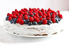 Creamy sweet cake with blueberries and raspberries. Creamy sweet cake with chocolate and cream, garnished with blueberries and raspberries Stock Photo