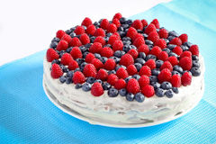 Creamy sweet cake. With chocolate and cream, garnished with blueberries and raspberries on a white tablecloth Stock Photo