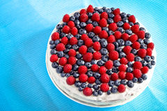 Creamy sweet cake. With chocolate and cream, garnished with blueberries and raspberries on a white tablecloth Stock Image