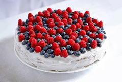 Creamy sweet cake. With chocolate and cream, garnished with blueberries and raspberries on a white tablecloth Royalty Free Stock Photo