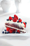 Creamy sweet cake. With chocolate and cream, garnished with blueberries and raspberries on a white tablecloth Royalty Free Stock Image