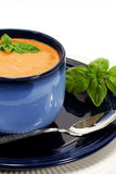 Tomato Soup Basil Spoon. Creamy tomato soup in blue bowl topped with fresh sprig of basil.The bowl is on a plate with a spoon, and the background is white Stock Photos