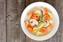 Creamy tortellini, mushroom soup in a white bowl over wood Stock Photos