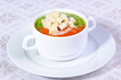 Creamy vegetable soup. Cup of creamy vegetable soup with croutons on tablecloth royalty free stock photos