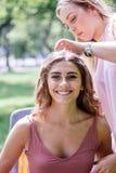 Crear el peinado agradable para la señora joven en el parque Fotografía de archivo libre de regalías