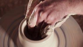 Crear la loza de barro y el concepto tradicional de la cerámica Las manos del alfarero de sexo masculino experimentado que crean  almacen de metraje de vídeo