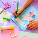 Crear una tarjeta de felicitación con las flores para la mamá El niño sostiene una pluma disponible y escribe el 8 de marzo step Imágenes de archivo libres de regalías