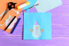 Crear una tarjeta de papel del invierno de los niños preceptoral Tarjeta de papel del muñeco de nieve, tijeras, marcadores, lápiz Foto de archivo libre de regalías