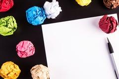 Creased бумаги цвета на черной таблице Стоковая Фотография