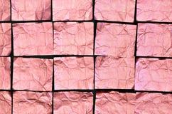 Creased розовые квадраты алюминиевой фольги на черной предпосылке Стоковое Фото