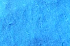 Creased blue cloth material fragment as a background textur. E royalty free stock photos