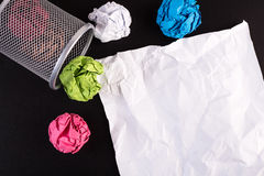 Creased color papers and office bin with crumpled white paper Stock Photos