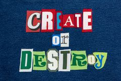 CREATE OR DESTROY text word collage colorful fabric on denim, encourage or discourage royalty free stock photography