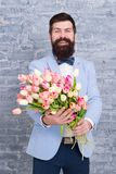 We create emotions. Bearded man with tulip bouquet. Love date. international holiday. Womens day. Flower for March 8. Spring gift. Bearded man hipster with stock images