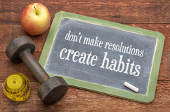 Create habits, not resolutions. Do not make resolutions, create habits - advice on a vintage slate blackboard with a dumbbell Royalty Free Stock Image