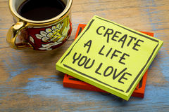 Create a life you love advice or reminder. Handwriting in black ink on a sticky note with a cup of coffee Stock Photos