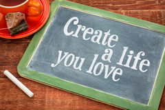 Create life you love motivational advice. Text  on a slate blackboard with chalk and cup of tea Royalty Free Stock Photo
