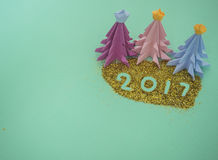 Create Merry Christmas. Colorful origami paper to make Christmas tree,  decorated on green background for creative Merry Christmas and Happy New year card Stock Image