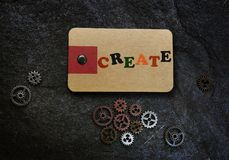 Create message and gears. Create message on tag with metal gears on dark textured background Stock Photography