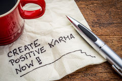 Create positive karma - text on napkin. Create positive karma now - motivational handwriting on a napkin with cup of coffee Royalty Free Stock Image