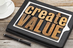 Create value on digital tablet. Create value - inspirational text in vintage letterpress wood type on a digital tablet with a cup of coffee Stock Image