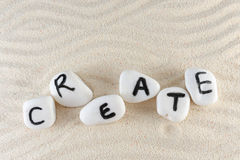 Create word. On group of stones with sand as background Stock Image