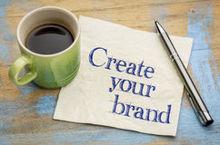 Create your brand advice - napkin. Create your brand advice - handwriting on a napkin with a cup of coffee stock image