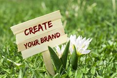 Create your brand. On wooden sign in garden with white spring flower royalty free stock photography