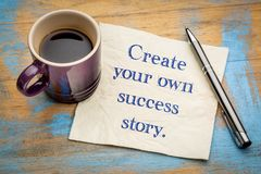 Create your own success story. Motivational handwriting on a napkin with a cup of espresso coffee Stock Photo