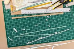 Creatief bureau met groene scherpe mat, snijder, potlood, band, regel stock foto