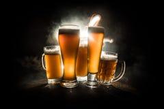 Creatief concept Bierglazen op houten lijst bij donkere gestemde mistige achtergrond royalty-vrije stock afbeeldingen