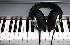 Creatief concept een digitaal pianotoetsenbord met grote zwarte leerhoofdtelefoons Royalty-vrije Stock Foto's