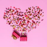 Creatief concept met feestelijk decor op roze achtergrond Confettienharten en sterren, rode linten Royalty-vrije Stock Afbeeldingen