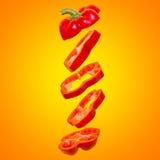 Creatief concept met vliegende oranje paprika Gesneden drijvende groene paprika op een oranje achtergrond Royalty-vrije Stock Afbeelding