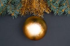 Creatief decoratiepatroon met groene en gouden Kerstboomtakken en grote snuisterij Concept royalty-vrije stock fotografie