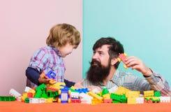 Creatief idee kleine jongen met papa het spelen E de bouwhuis met aannemer Kind stock afbeelding
