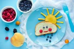 Creatief ontbijtidee voor jonge geitjes - broodbroodje met fruit en berr Stock Afbeeldingen