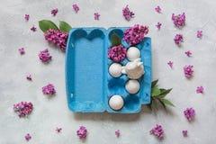 Creatief pak eieren met konijn en decoratieve lilac bloemen lichte achtergrond Het Concept van Pasen royalty-vrije stock foto's