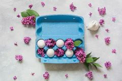 Creatief pak eieren met konijn en decoratieve lilac bloemen lichte achtergrond Het Concept van Pasen royalty-vrije stock afbeelding