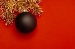 Creatief patroon met gouden Kerstboomtakken en grote zwarte snuisterij stock foto's