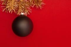 Creatief patroon met gouden Kerstboomtakken en grote zwarte snuisterij Concept royalty-vrije stock afbeeldingen