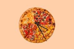 Creatief pizzabeeld in de vorm van een klok met pijlen op een mooie heldere achtergrond levering 24 ureninschrijving Stock Foto