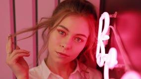 Creatief portret van mooi meisje dichtbij rode neonlichtmuur stock footage